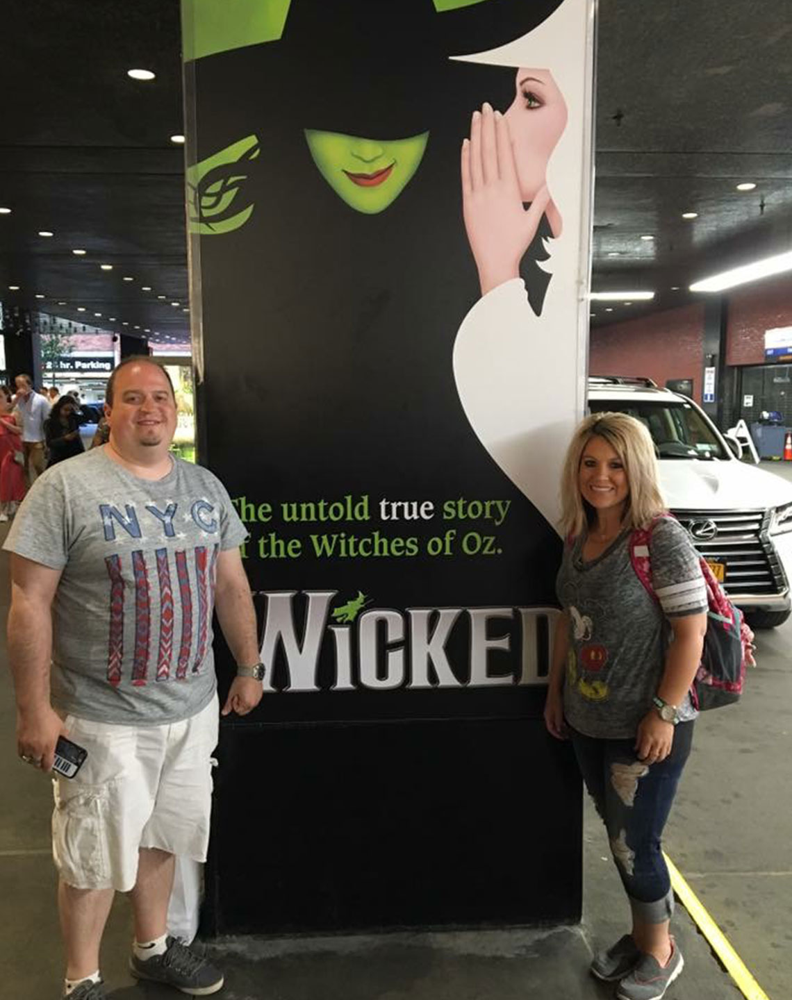 Director Brian Saylor and his wife Becky and by the Wicked sign on Broadway.