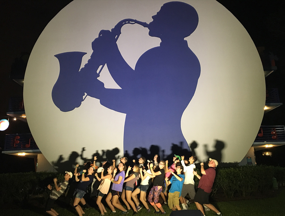 Teri Aitchison sharing a memory with Trojan Marching Band sax line at Disney's All Star Music Resort.