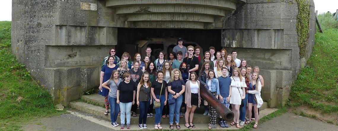 The Pendleton Heights Choir in front of a German bunker along the Atlantic Wall in Normandy.
