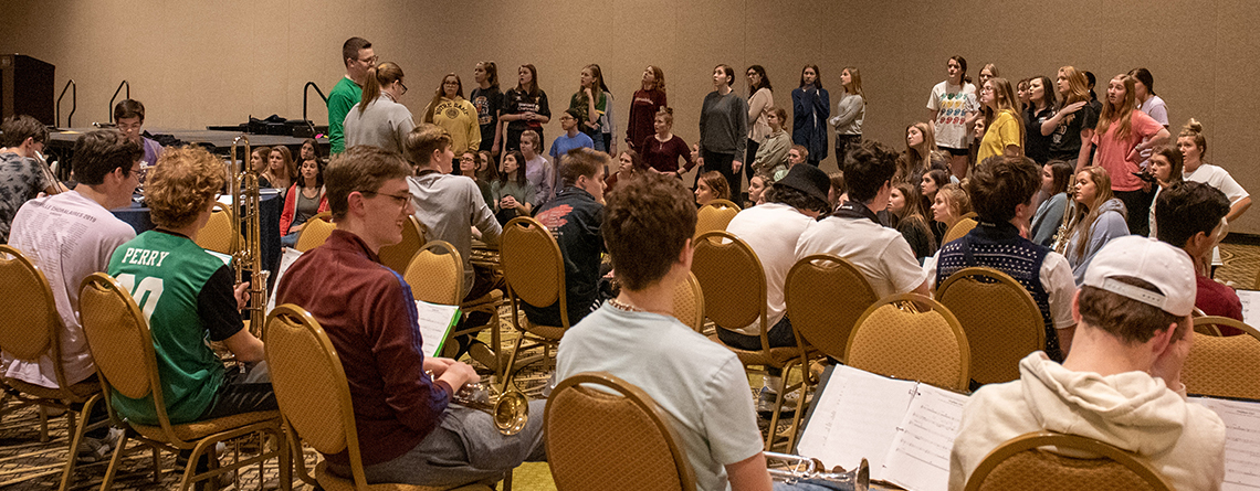 Students work through a portion of the competition show in a hotel ballroom. Both choirs were finalists and went on to win their divisions.