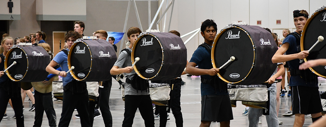 The bass drum line works through a section of the show. Students are held accountable to a high level of performance.