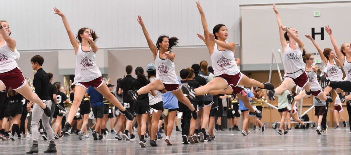 Vision Dance Company members fly high during a rehearsal in one of the convention center halls. The students continued to refine the program throughout the BOA Grand Nationals weekend.